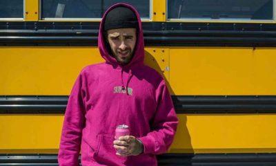 Quebonafide w różowej bluzie Supreme przy autobusie