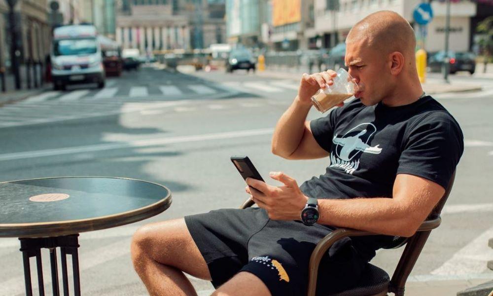 hinol w czarnej koszulce pije kawę
